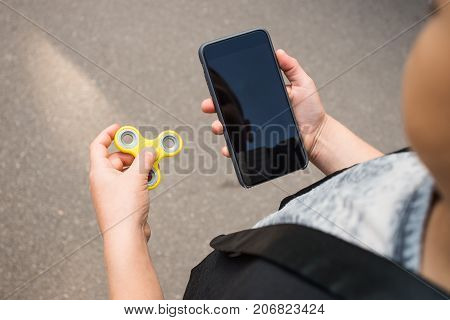 Boy's hands with mobile telephone and spinner. Beautiful boy in casual wear