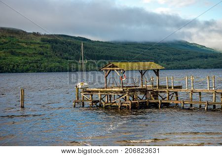 A wooden jetty with a life buoy at Loch Tay central Scotland
