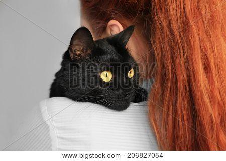 Woman holding black cat. Adoption concept