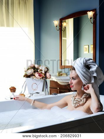 Luxury fashion brunette woman in hotel spa lying in bath tub with bouquet of flowers looking at the corner
