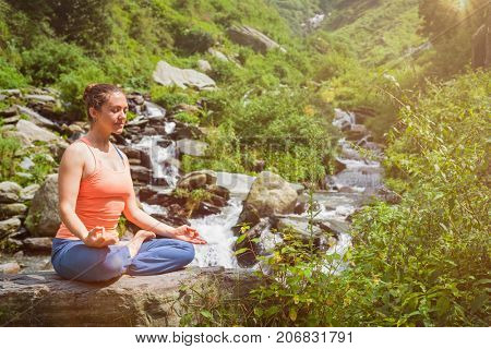 Woman in Hatha yoga asana Padmasana lotus pose outdoors