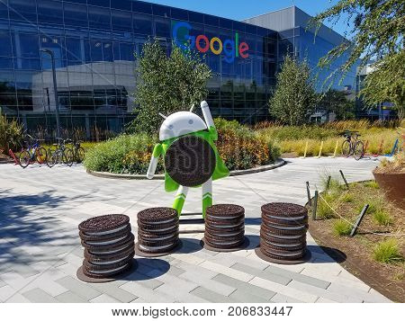 MOUNTAIN VIEW CA/USA - August 28 2017: Figure of Android Oreo Android 8 in front of Googleplex waving to visitors. One of Google buildings is in the background.