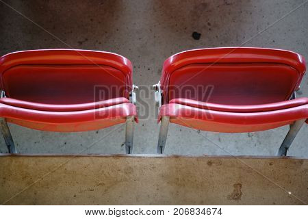 Two adjoining chairs on the stadium of a sports stadium.