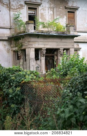 An old abandoned and run-down villa with unkempt front yard.