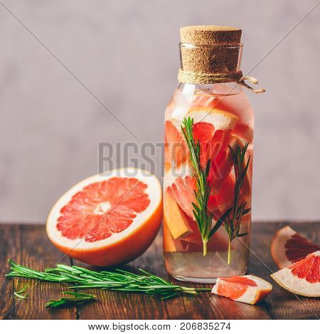 Bottle of Detox Water Infused with Sliced Raw Grapefruit and Fresh Springs of Rosemary. And Ingredients on Wooden Table.