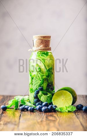 Bottle of Infused Water with Lime Mint and Blueberry and All Ingredients on Table. Copy Space and Vertical Orientation.