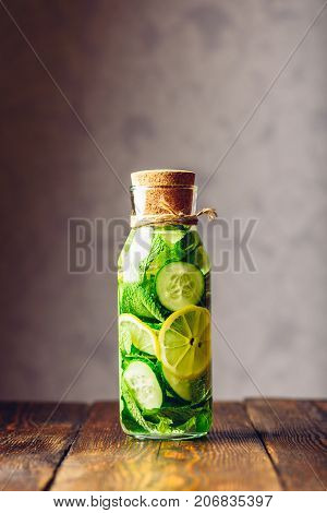 Detox Water Infused with Sliced Lemon Cucumber and Fresh Sprigs of Mint. Copy Space on the Top. Vertical Orientation.