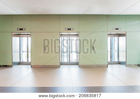 Open and closed chrome metal office building elevator doors.