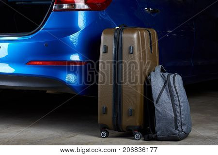 Baggage bags loading to car trunk close-up. Loading luggage in modern blue car
