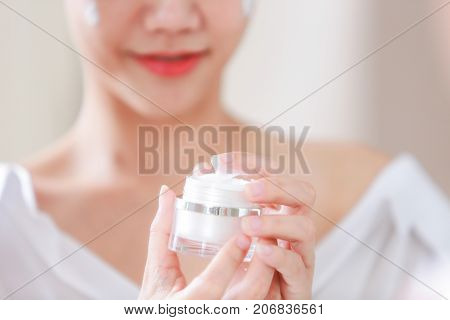 Young woman applying moisturizer on her face and holding jar of skin cream and lotion.