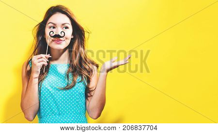 Young woman holding paper party sticks on a yellow background
