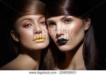 two beautiful young women with yellow and black lips makeup and long straight glossy hair. beauty shot black background. copy space.
