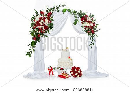 beautiful traditional white wedding cake with bone decor for dog wedding party standing under flower archway. studio shot. copy space.