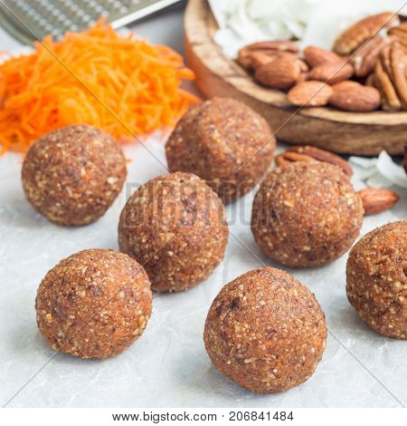 Healthy homemade paleo energy balls with carrot nuts dates and coconut flakes on a parchment square format