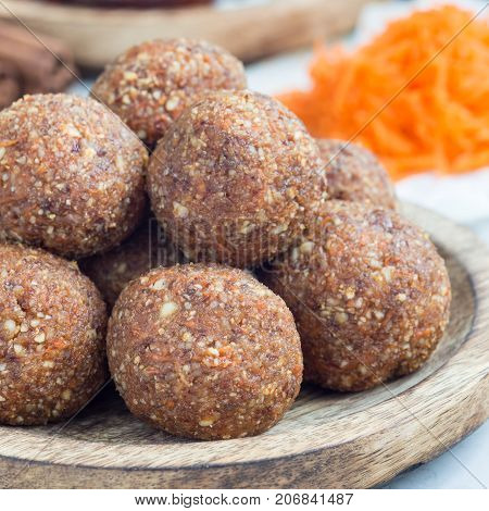 Homemade paleo energy balls with carrot nuts dates and coconut flakes on a wooden plate square format