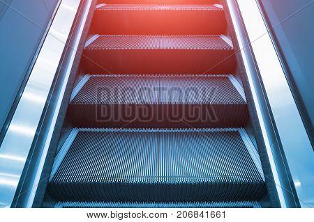 Escalator and step inside building, blue color tone.