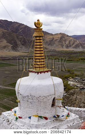 White stupa at Yumbulakhang Palace, first building of Tibet, on the hill overlooking the rice field of Yarlung valley in Tsetang city - Tibet