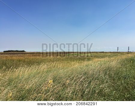 Railway Track and Meadow on Canadian Prairie Under Blue Sky