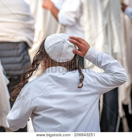 A young Jewish Hasid boy in a traditional headdress of a kippah and with long payos.
