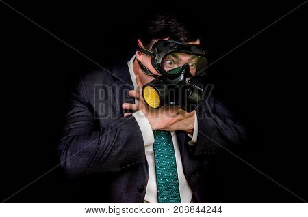 Businessman with gas mask can not breathe bad air - isolated on black