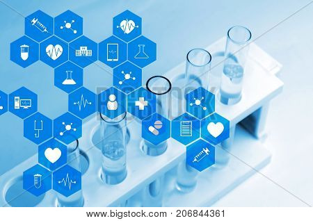 top view of chemical liquid in laboratory test tube with medical icon in hexagon pattern blue color tone laboratory science chemical and medical research concept soft and selective focus