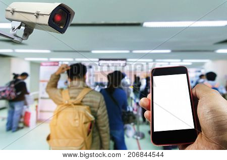 hand using smart phone monitoring and CCTV security indoor camera system operating in airport with people queue at immigration control background surveillance security and safety technology concept