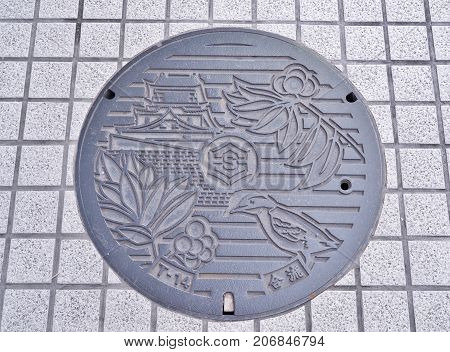 Kochi, Japan - July 19, 2016: Manhole cover of Kochi city engraved with Kochi castle, Winter-hazel, Japanese wagtail and chinaberry tree. They are symbols of Kochi Prefecture, Shikoku, Japan.