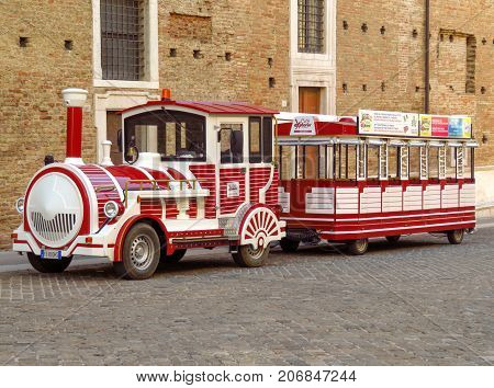 Urbino Italy - June 24 2017: Funny steam locomotive with train cars near Ducale Palace in old town