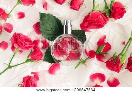 Feminine perfume bottle top view on wrapping gift paper, rose flowers, petals, leaves scattered around.