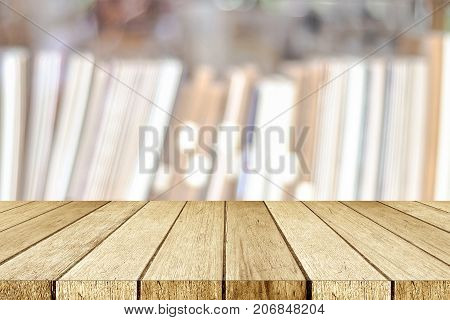 Empty perspective wood table shelf over blur bookshelves at book store background for product display montage education concept