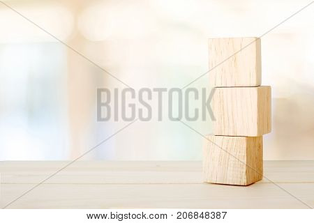 Three wooden cubes on table over blur abstract bokeh light background banner with copy space for text
