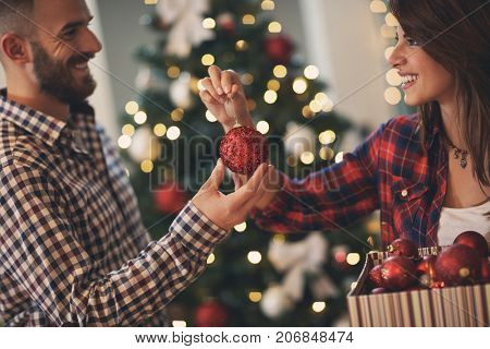 Happy couple in love decorating Christmas tree
