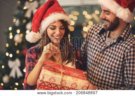 Cheerful man and woman opens Christmas gift
