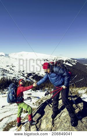 Climber helping teammate climb the man with the backpack reached out a helping hand to his friend.