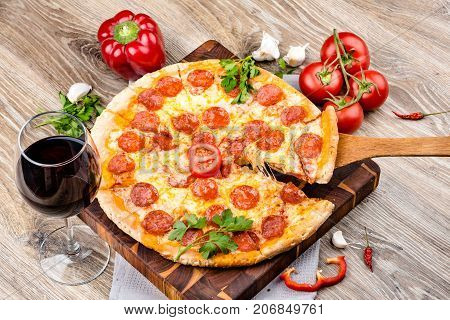 Photo of a hot pizza on wooden background