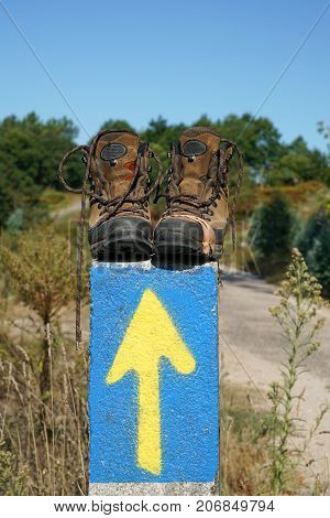 Broken walking shoes on the top of a waymark along the Way of St. James, Spain, Europe