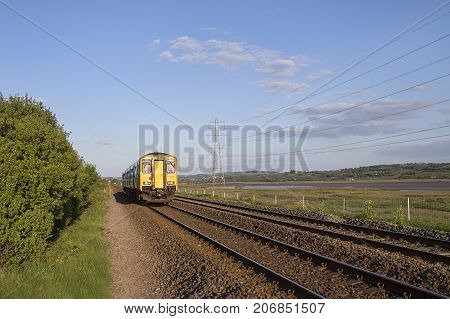 Swansea, UK: May 04, 2017: Arriva train traveling on a local line along side some pylons. Arriva Trains Wales is a British train operating company operating the Wales & Borders franchise
