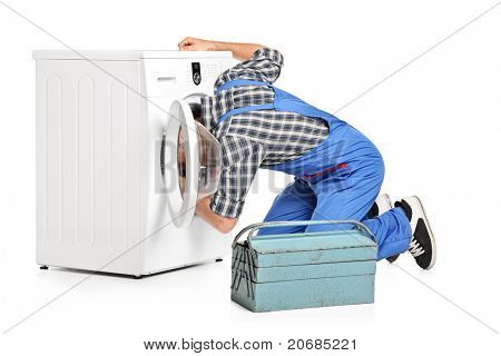 A repairman trying to fix a washing machine isolated on white background