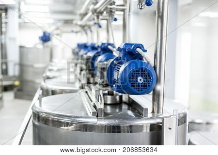 Rows of blue electric motors on tanks for mixing liquids. Stainless steel, food industry.
