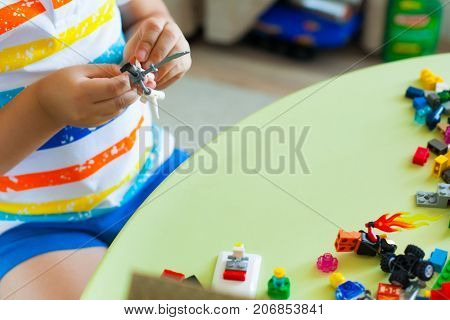 Little Blond Kid Boy Playing With Lots Of Colorful Plastic Blocks Indoor. Blocks Of Lego Are Sorted.