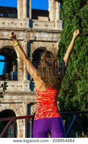 Modern Sportswoman Near Colosseum In Rome, Italy Rejoicing