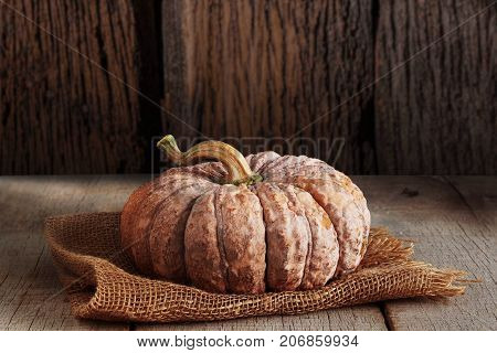 Pumpkin on sackcloth with a wood background.