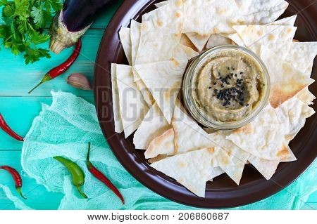 Light dietary pate from eggplant. Baba ganush is an Asian dish. Serve with thin lavash on a ceramic bowl. Top view.