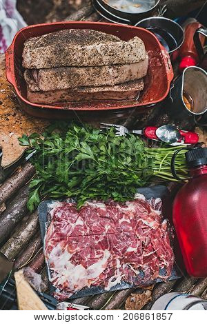 Raw steaks with flavoring jamon and parsley on table in forest