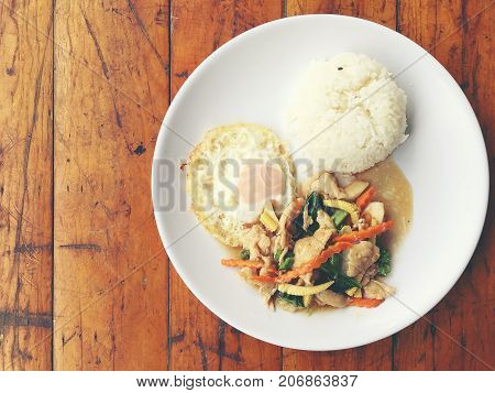Fried Chicken Stir Fry With Rice And Chinese Vegetables With Rice And Fried Egg In White Plate On Wo