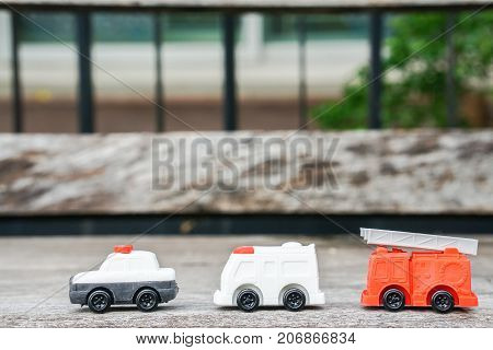 toy model of police car ambulance van and electricity and utility service truck for kid on wooden floor