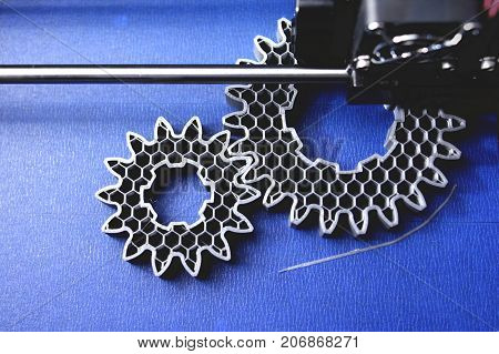 FDM 3D-printer manufacturing spur gears from silver-gray filament on blue print tape - top view on object, print bed and print head - matte look
