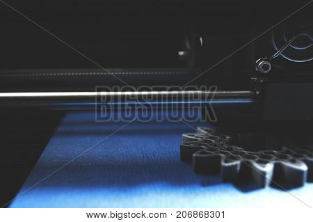 FDM 3D-printer manufacturing spur gears from silver-gray filament on blue print tape - dimmed part view on print head, print bed and object - blue shade