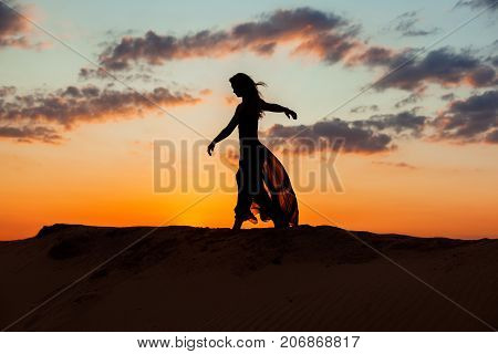 Silhouette of a woman during a dance at sunset.