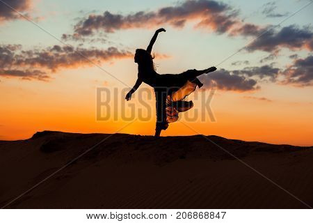 Ballerina is dancing against the backdrop of a sunset red sky.
